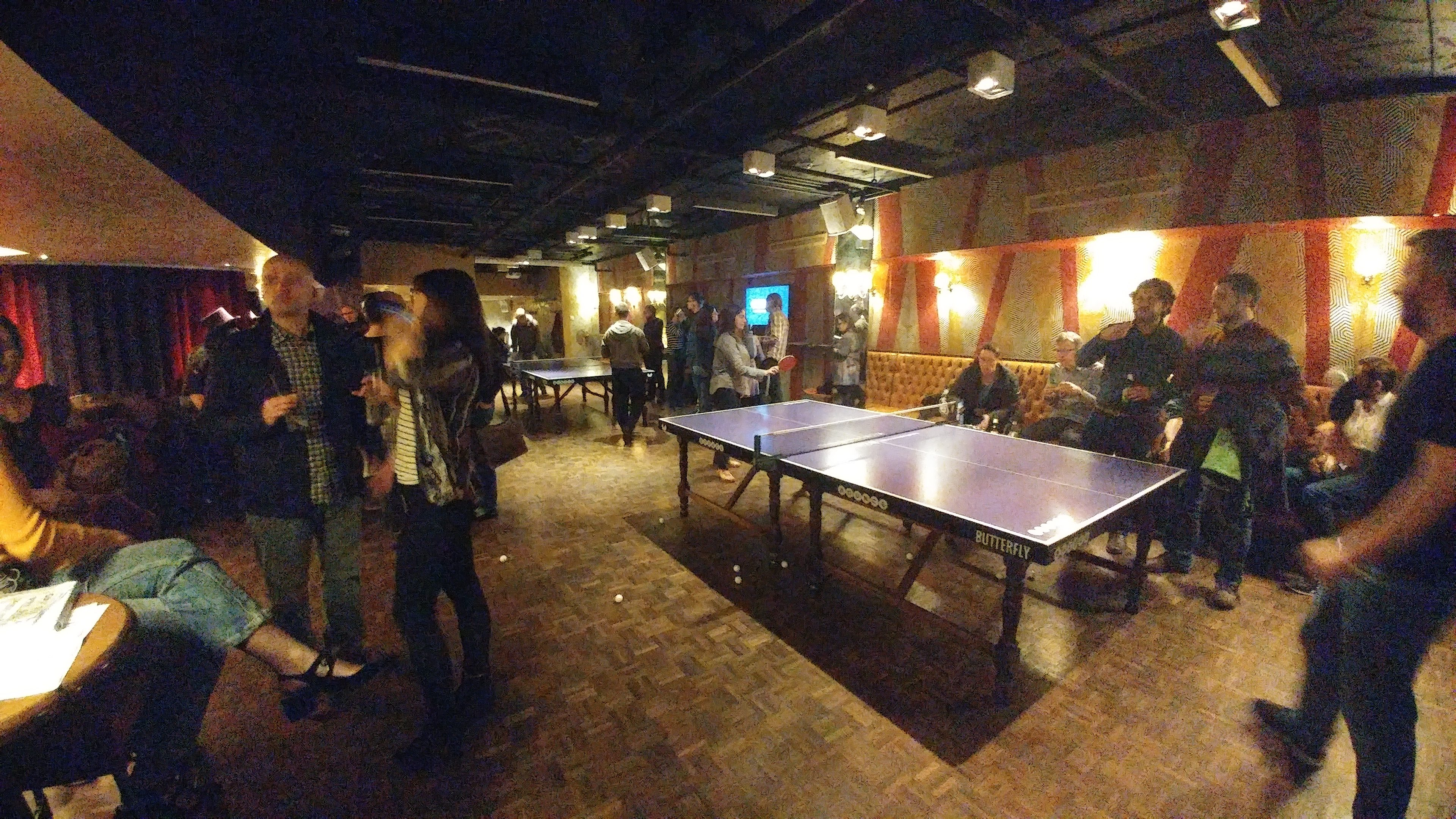 Volunteer, speaker and organiser event with people playing ping pong.